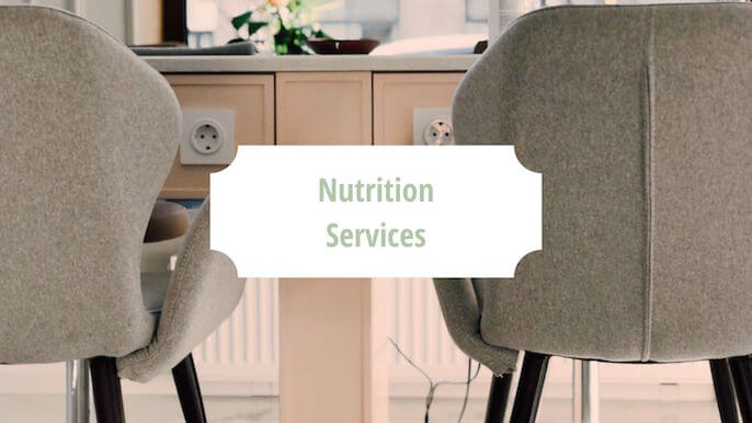 """Office with 2 chairs and the words """"Nutrition Services"""" in green over a white block 